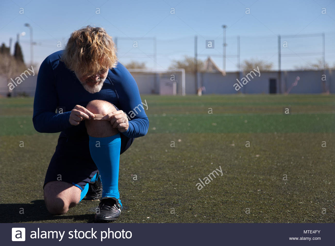 Football player puts a band-aid on his knee - Stock Image