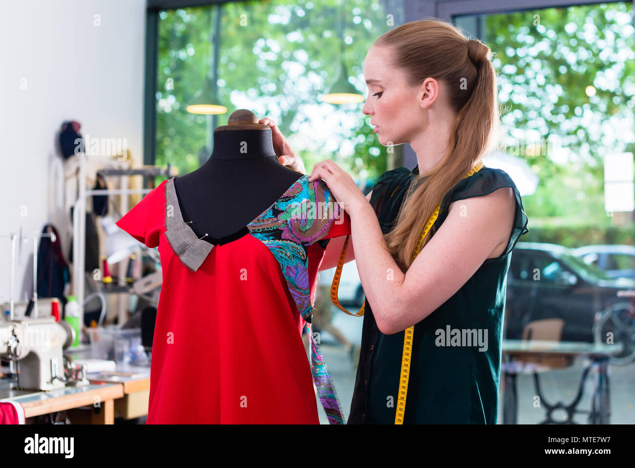 Fashion designer draping dress on mannequin - Stock Image