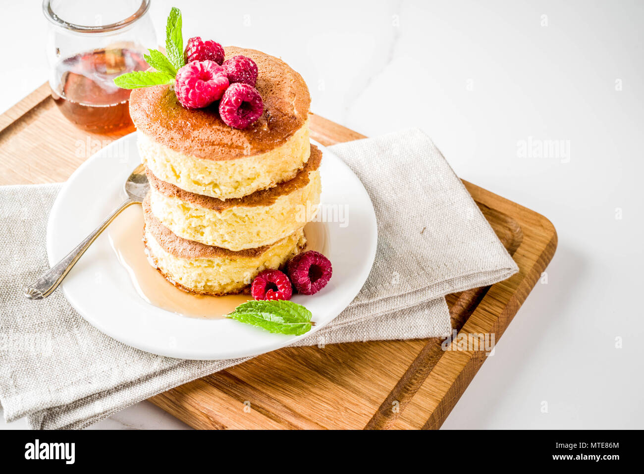 Trendy asian food, Fluffy Japan souffle pancakes, hotcakes with maple syrup and raspberry light concrete background copy space - Stock Image