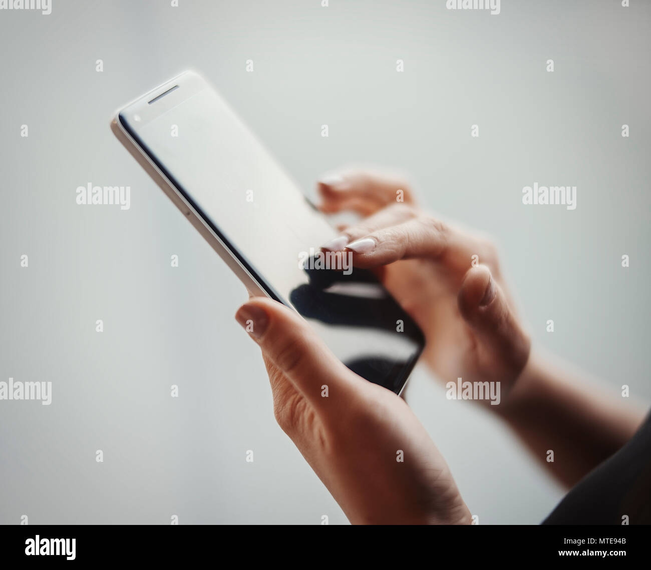 Young girl holding mobile phone and unlocking it - Stock Image