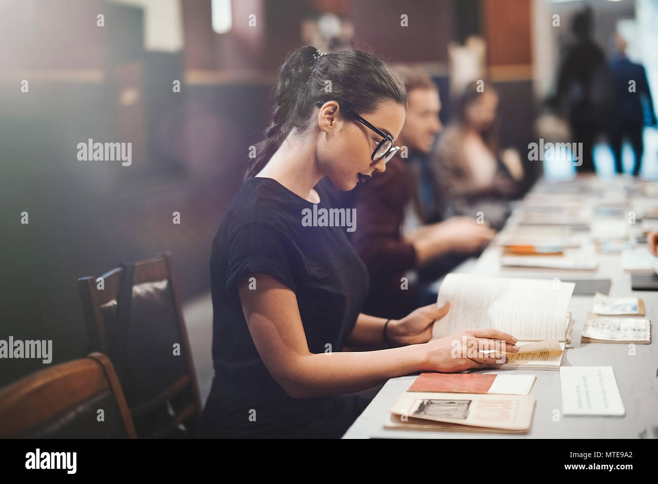 Young brunette girl with glasses and black lipstick reading book - Stock Image
