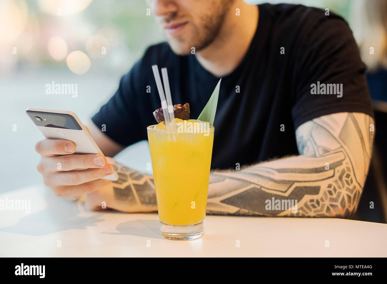 Attractive young man is holding mobile phone and drinking lemonade. - Stock Image