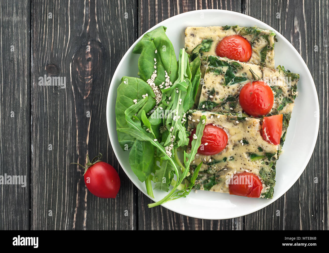 Frittata with spinach and tomatoes - Stock Image