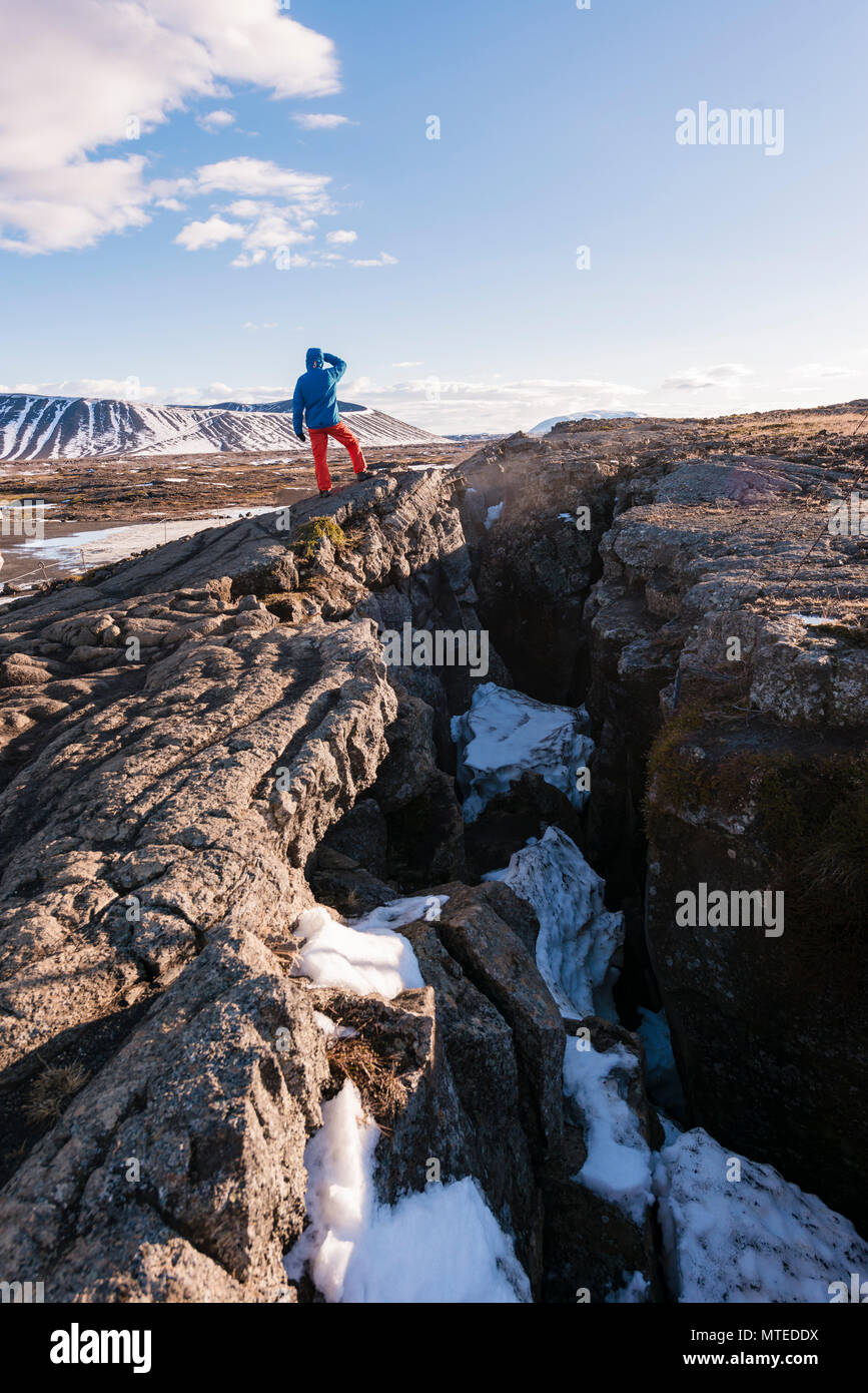 Man looking out, standing at continental fissure between North American and Eurasian Plate, Mid-Atlantic Ridge, Rift Valley - Stock Image