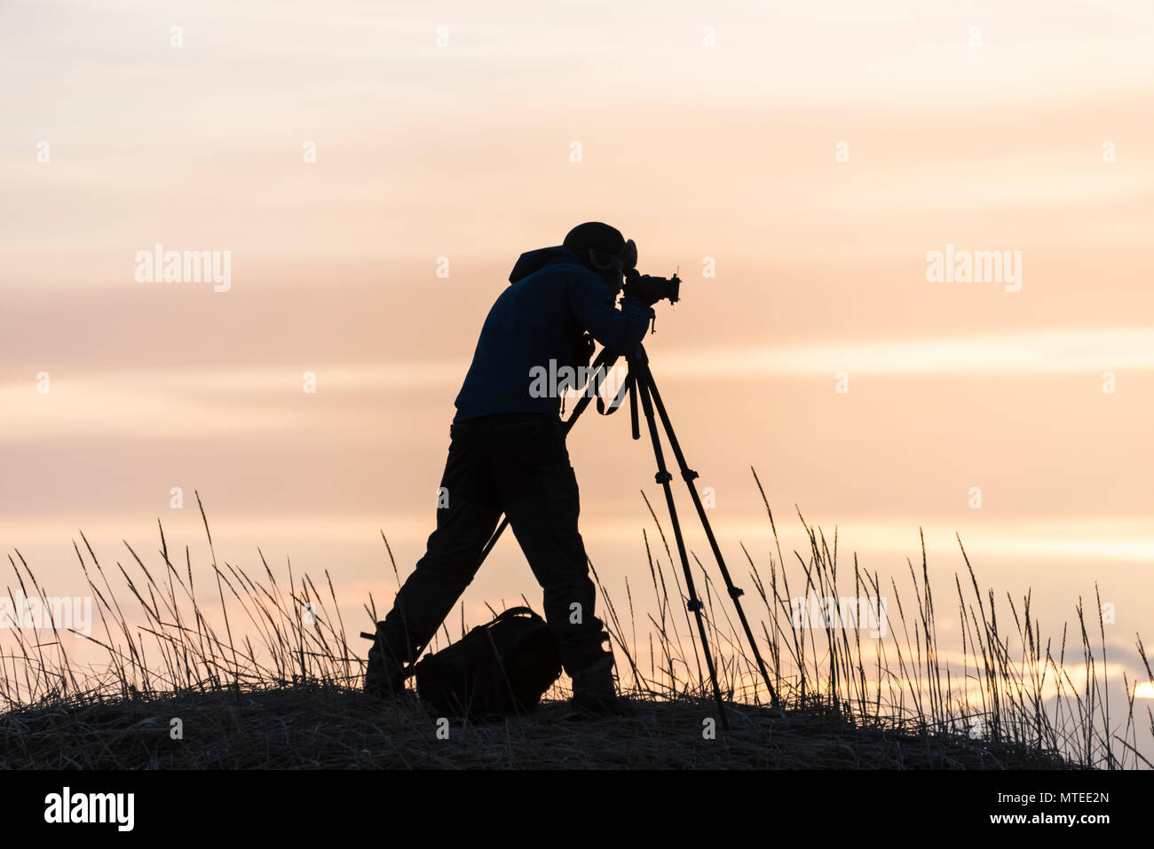Silhouette of a photographer with tripod, sunset, near Stokksnes, Iceland Stock Photo
