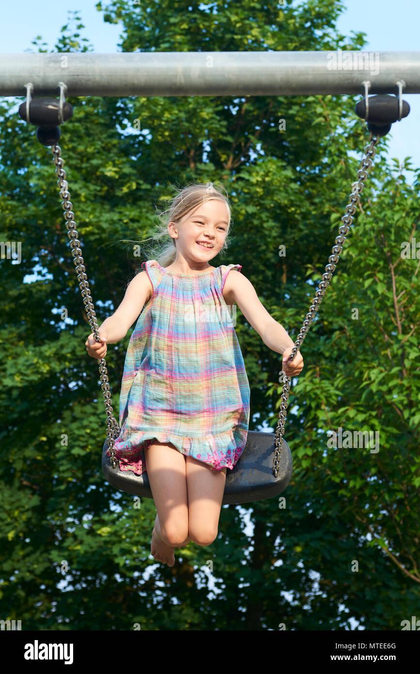 Little Child Blond Girl Having Fun On A Swing Outdoor Summer
