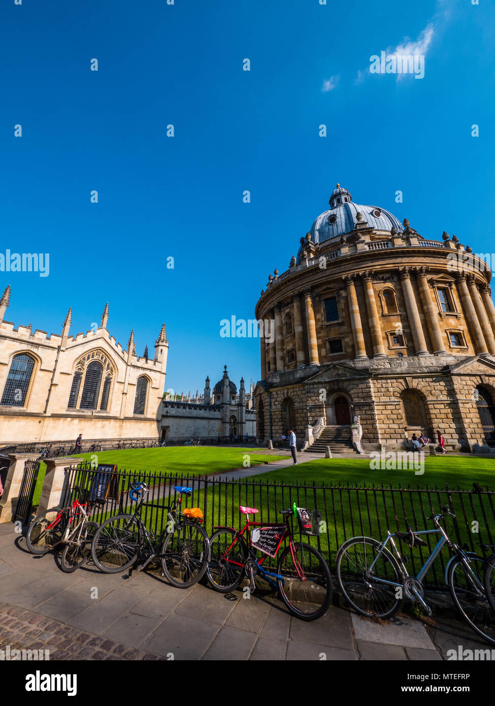 Bicycles on Railings Outside Radcliffe Camera, with all Souls College to the left, University of Oxford, Oxford, Oxfordshire, England, UK, GB. - Stock Image