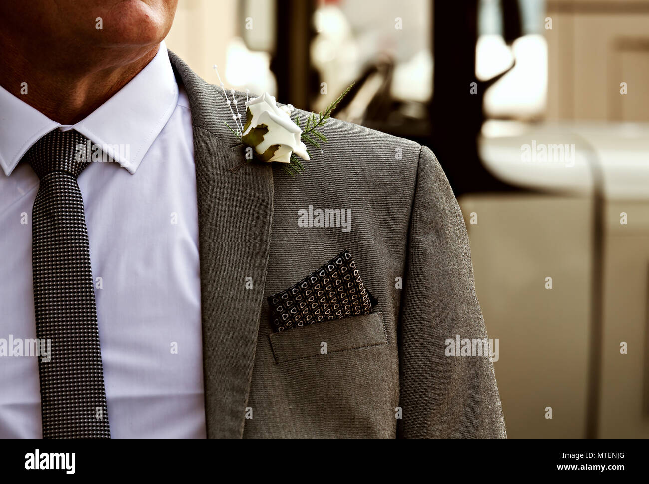 Smartly dressed man in a suit, shirt and tie with a white rose in his lapel at a wedding, could be the groom, father of the bride or best man. Stock Photo