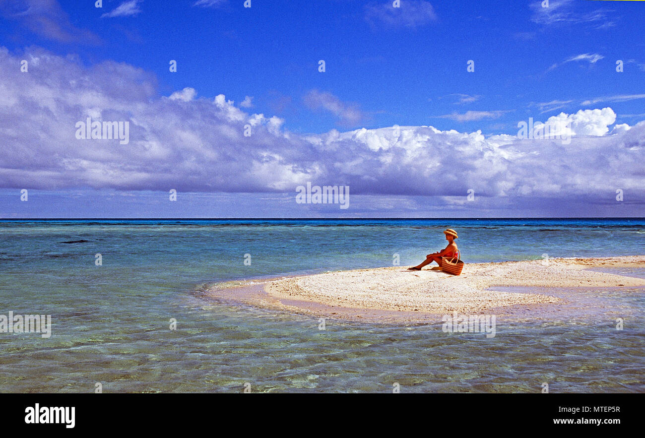 A single sunbather enjoys the quiet surf of a tiny island in the Tuamotu Archepelago in the French Polynesia region of the South Pacific Ocean. - Stock Image