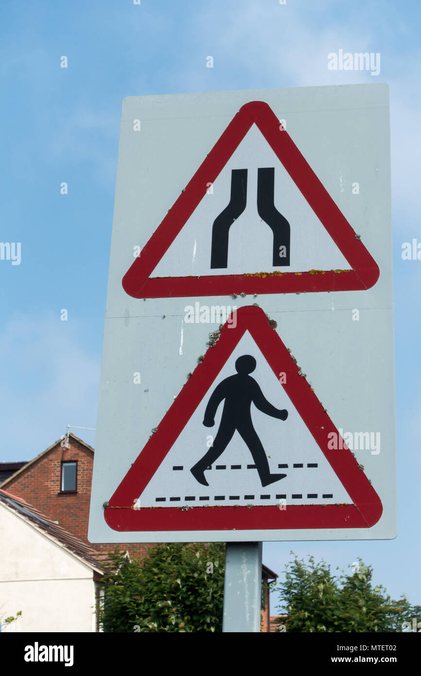 English road traffic triangular warning  signs for road narrows and zebra crossing, United Kingdom - Stock Image