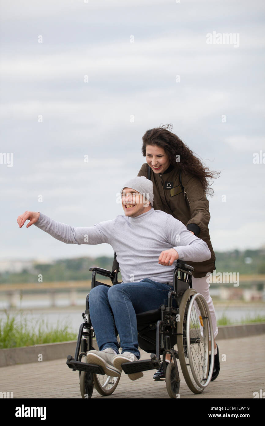 Disabled man in a wheelchair with young woman walking at the city street - Stock Image