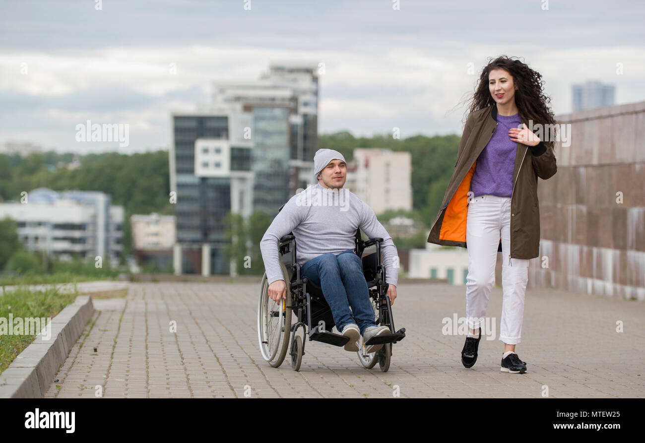 Happy couple - disabled young man in a wheelchair with young woman enjoying the sunset together - Stock Image