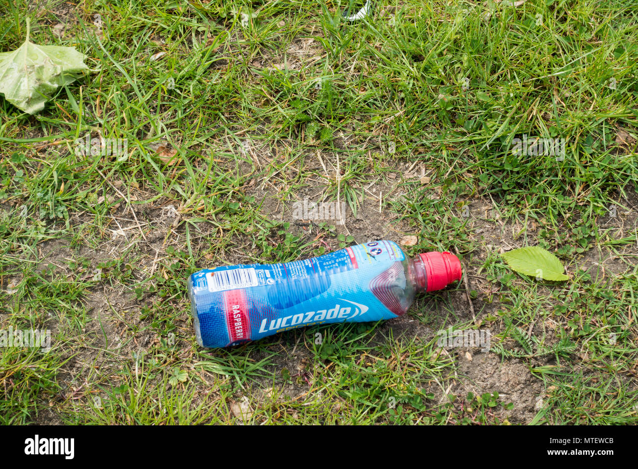 A plastic Lucozade bottle that has been thrown away onto some grass, Dorset, England, United Kingdom - Stock Image