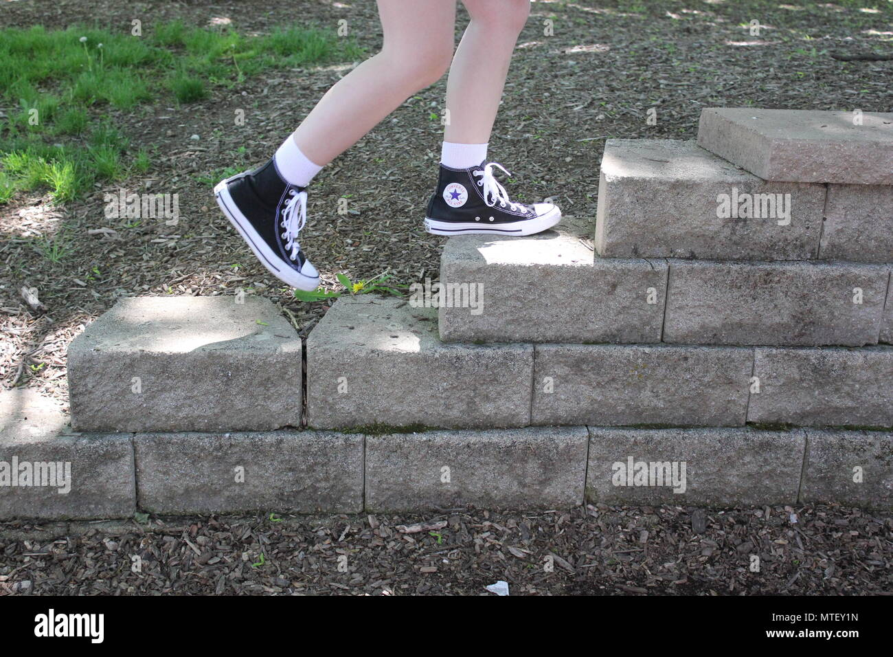 c1de4d3422 Teenaged girl walking up and down the stairs wearing white socks and a pair  of black converse sneaker high-tops.