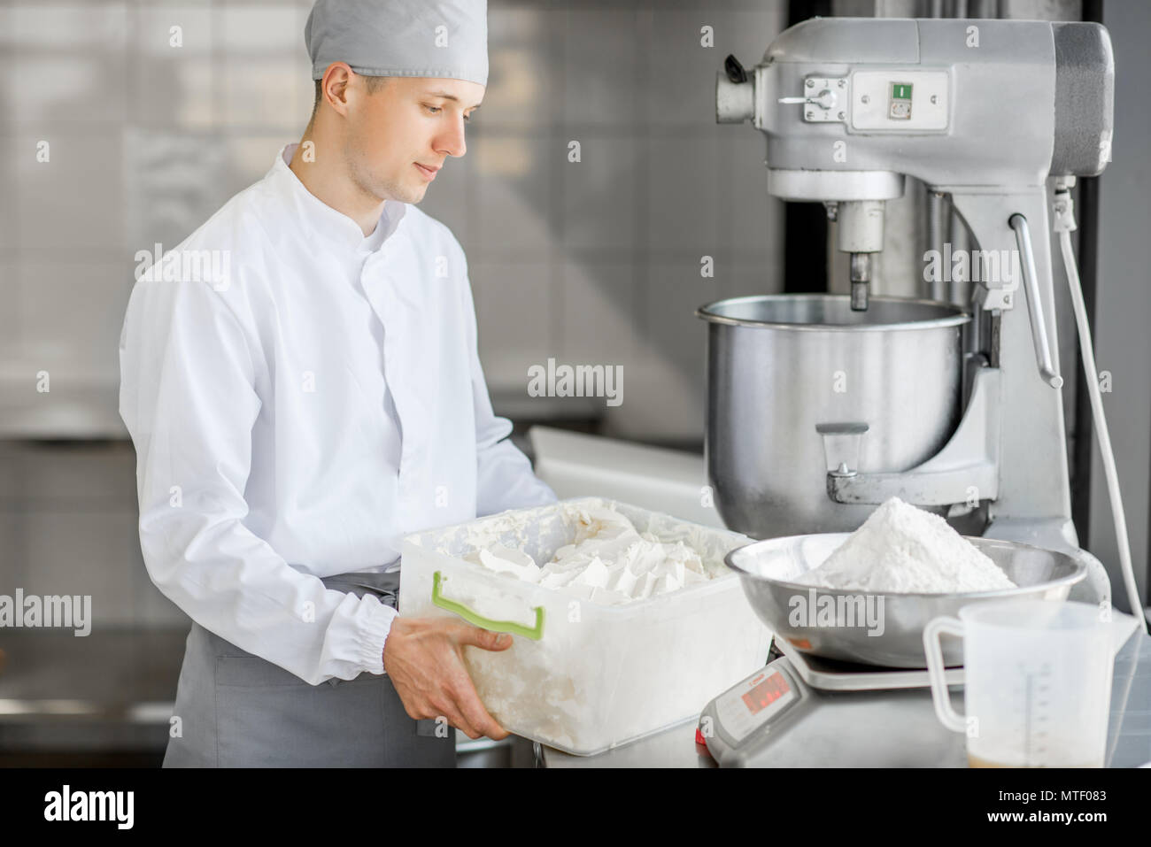 Man confectioner holding container with butter weighing ingredients for pastry at the bakery manufacturing - Stock Image