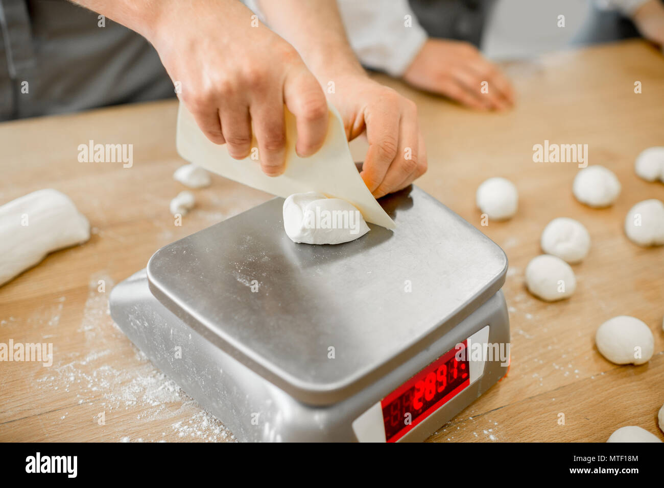 Baker weighing dough portions for baking buns at the manufacturig, close-up view - Stock Image