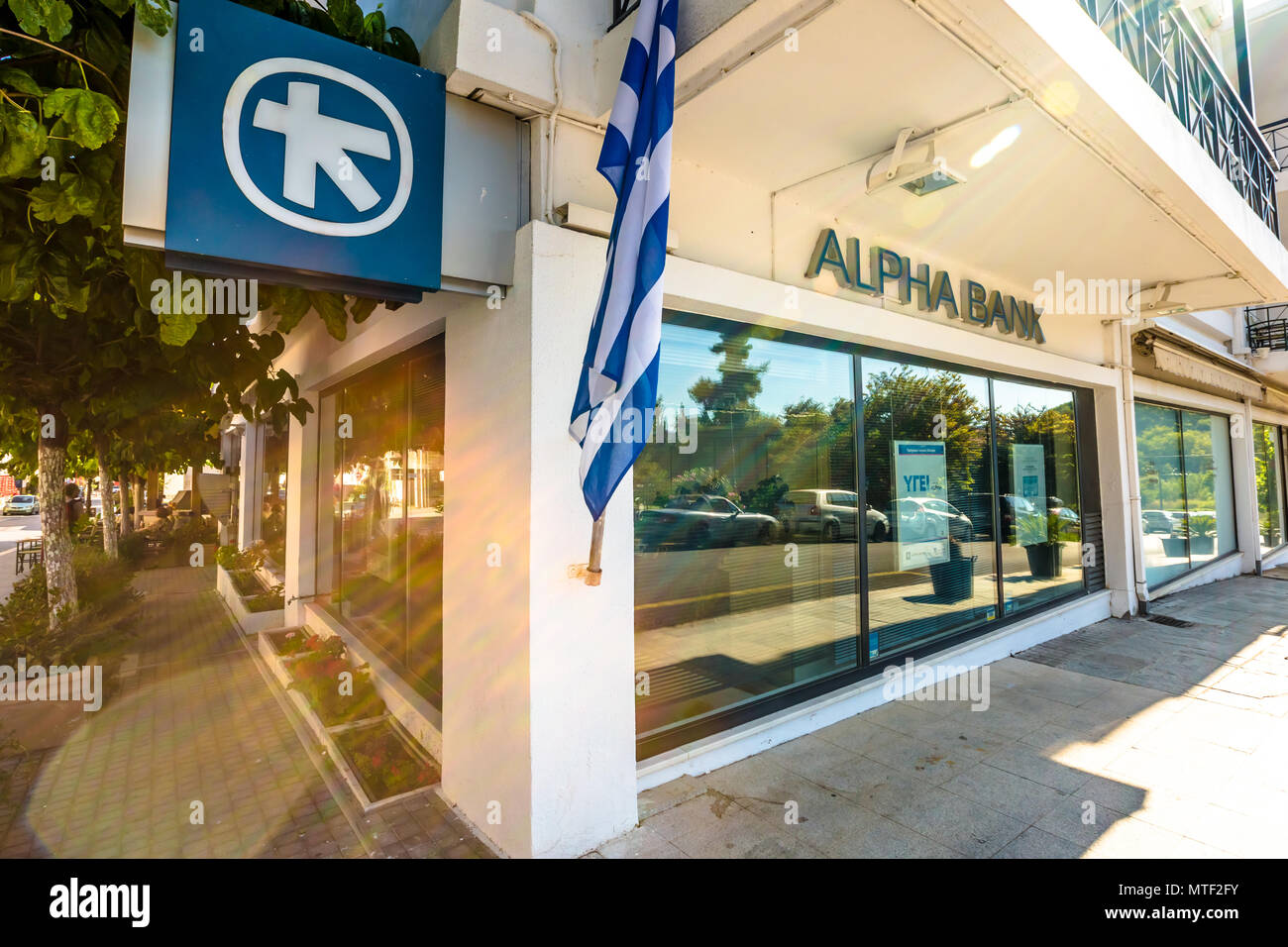 Olimpia town, Peloponnese, Greece - August 19, 2015:  Greek bank window with ATM and flag of Greece of the local Alpha Bank - Stock Image