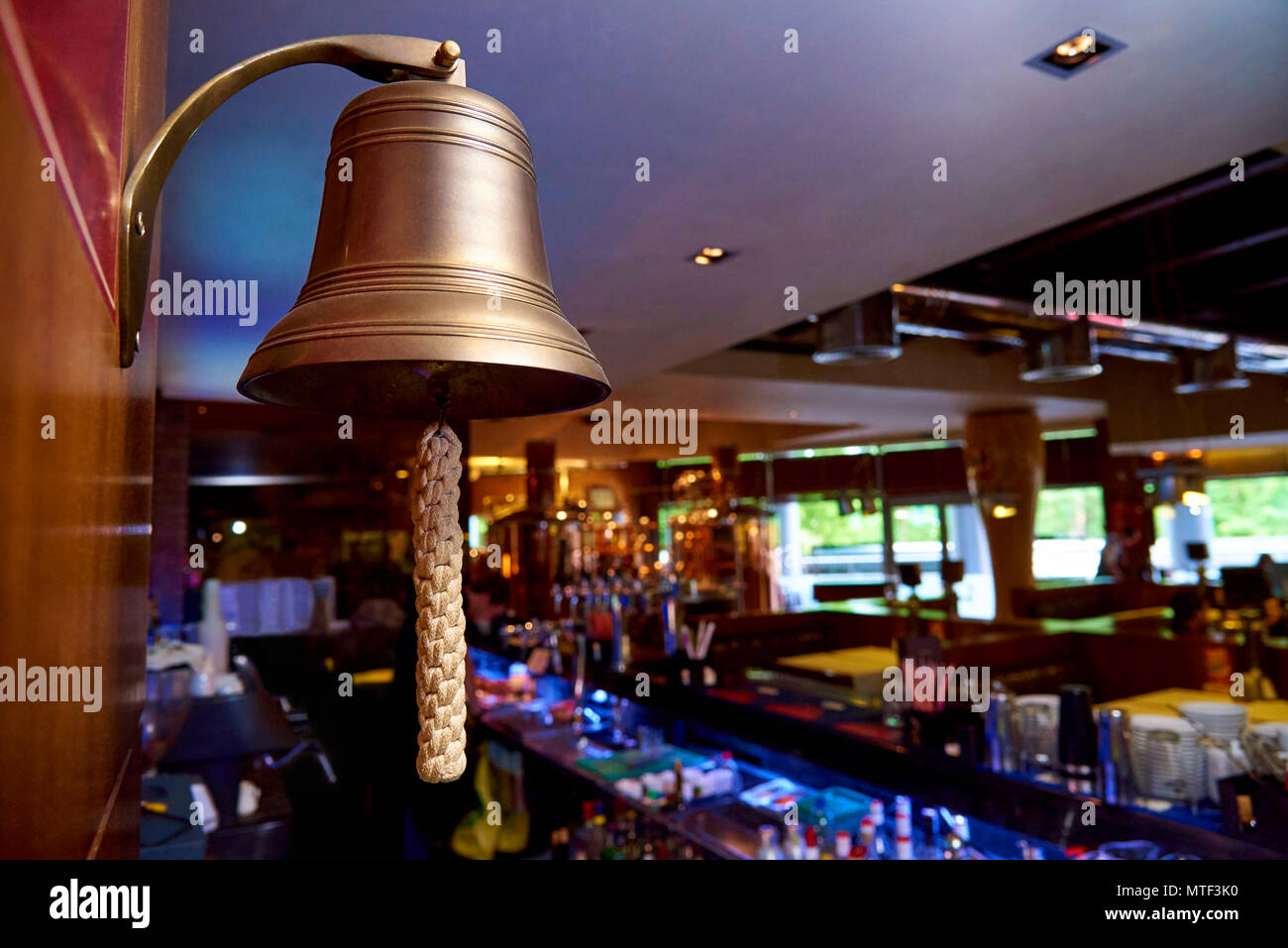 A bell with a woven rope on the background of the bar. - Stock Image