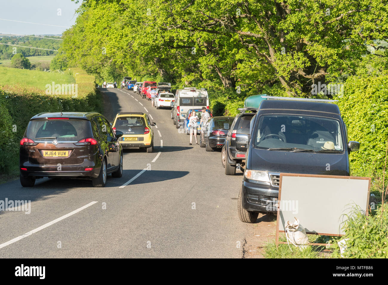 Tourist pressures and car parking problems - cars parked along the B834 road as people visit The Devils Pulpit Finnich Glen, Killearn, Scotland, UK - Stock Image