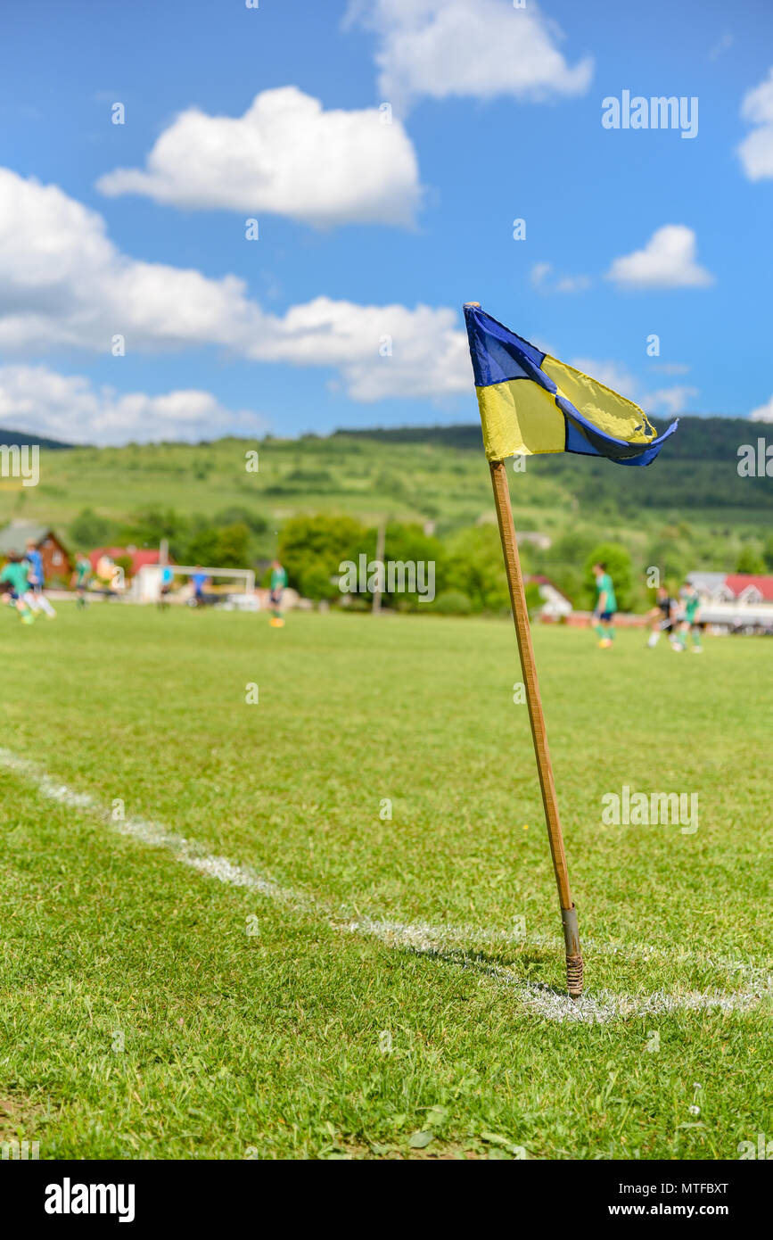 Amateur soccer field, retro corner flag on the foreground, football players are fighting for the ball on the background. Stories about rural life in U - Stock Image