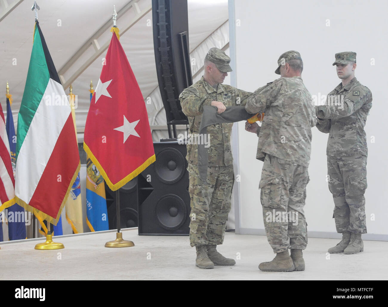 Col. Ryan Pace and Command Sgt. Maj. Thomas Mize case the 77th Combat Aviation Brigade Colors during their Transfer of Authority Ceremony on April 23. The TOA signals the transference of responsibility for theater aviation operations to the incoming 29th CAB at Camp Buehring, Kuwait (US. Army - Stock Image