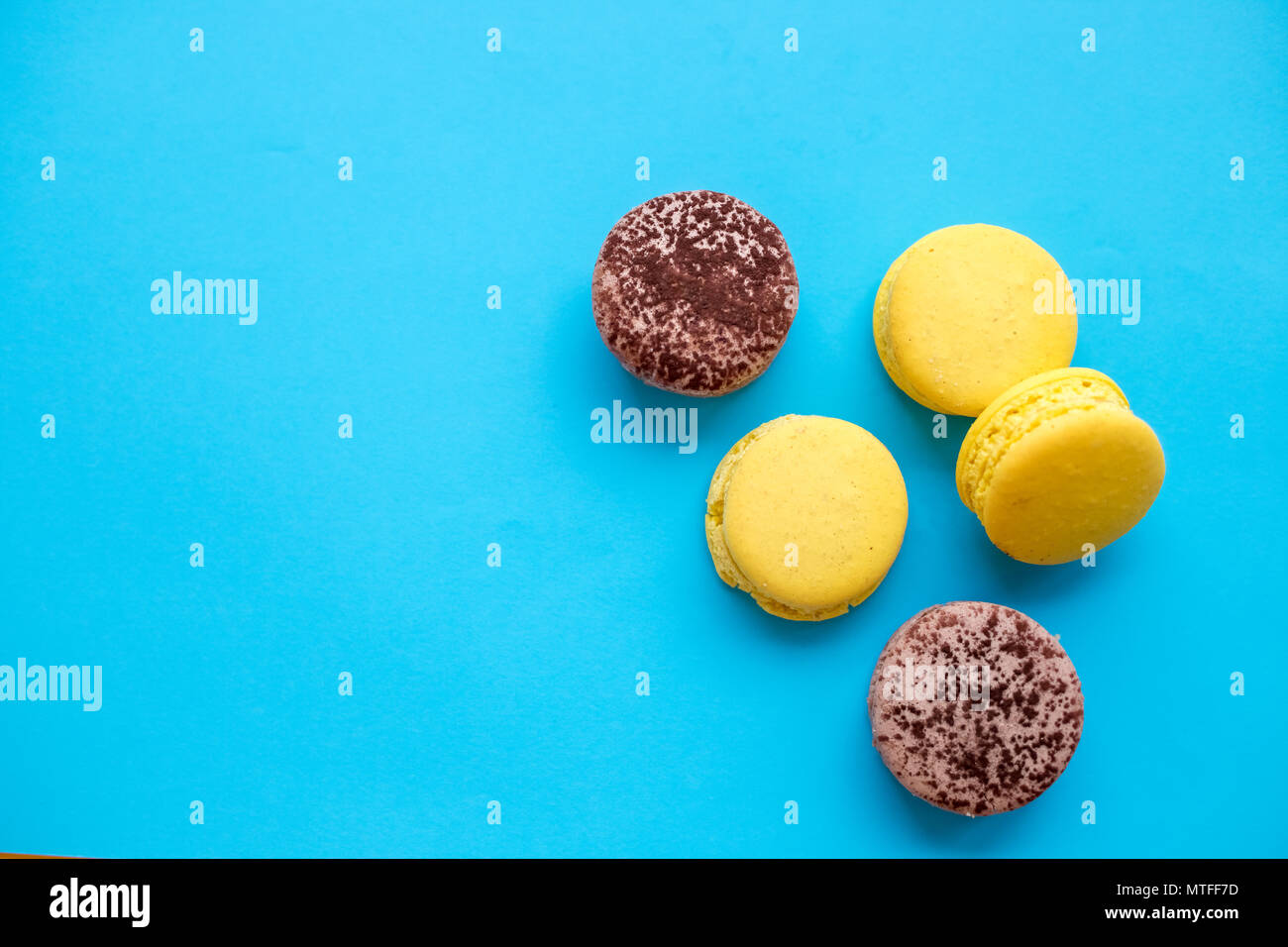 Colorful macarons cake, top view flat lay, sweet macaroon on color blue candy isolated background. Minimal concepts pattern above, food background. Copy space . French dessert. - Stock Image