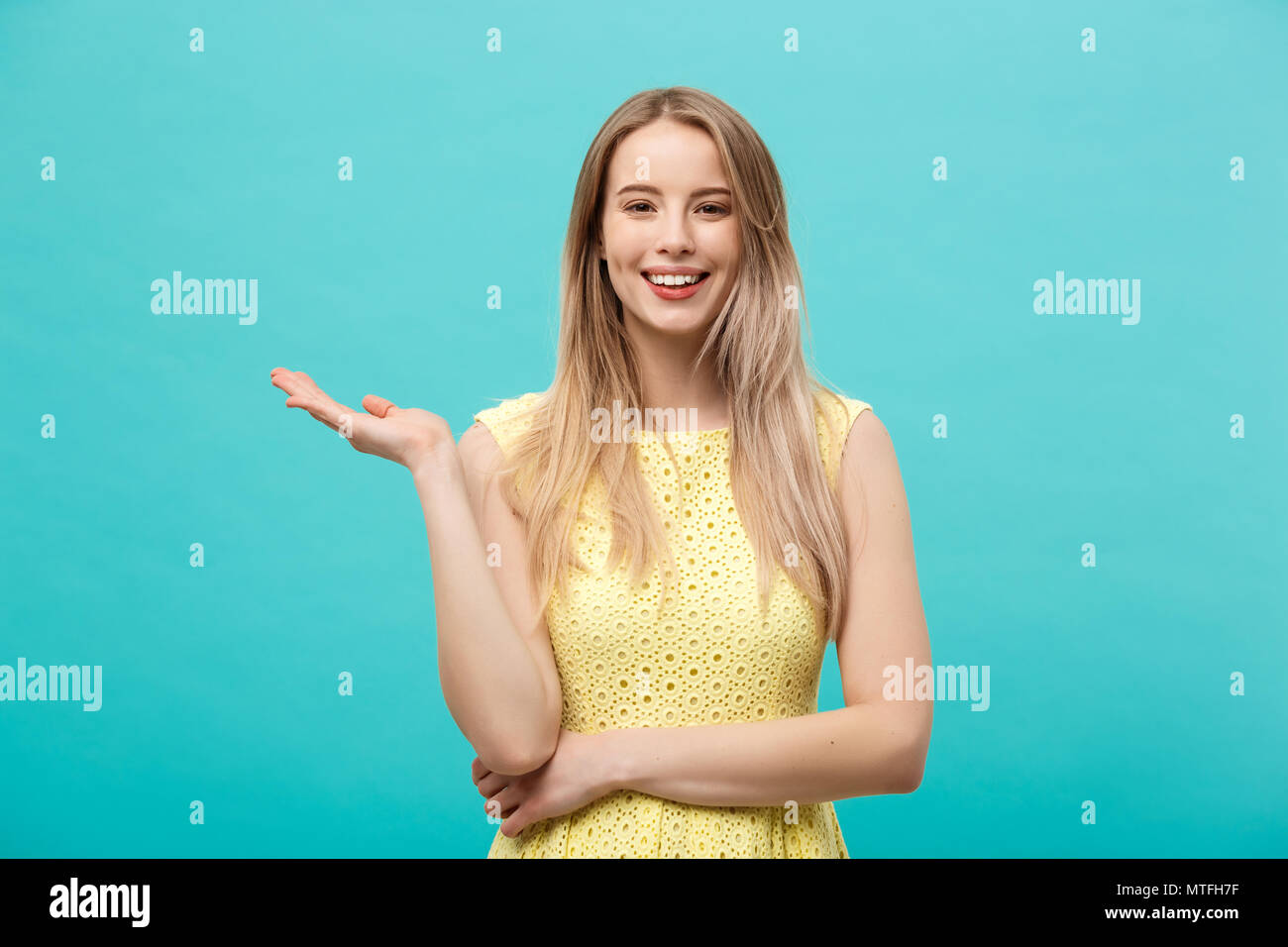 Portrait of stylish, nice, cute, caucasian woman with hairstyle in yellow dress holding in hand on empty places, copy spaces on her palms, looking at camera, isolated on blue background - Stock Image