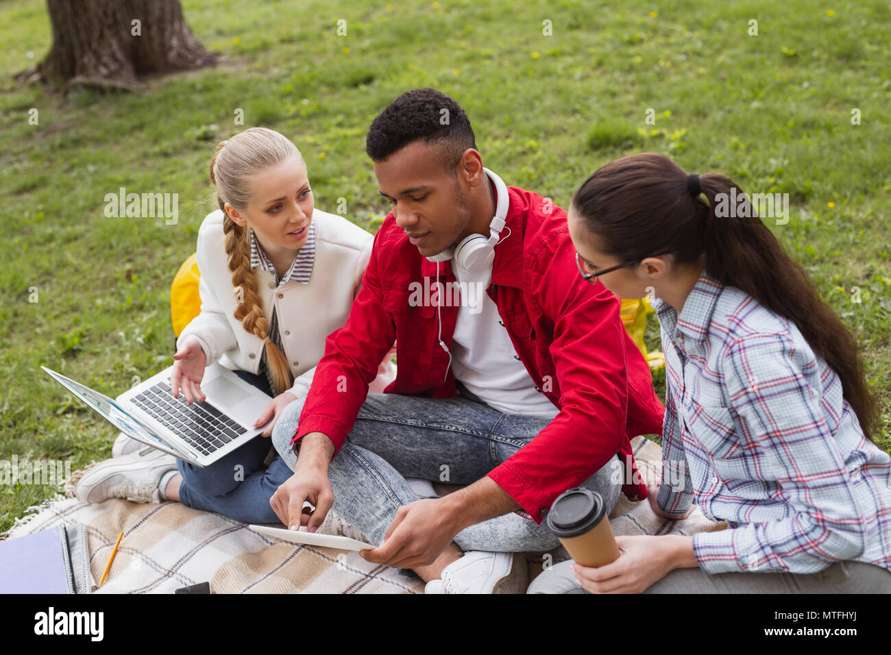 Three young students discussing their student life - Stock Image