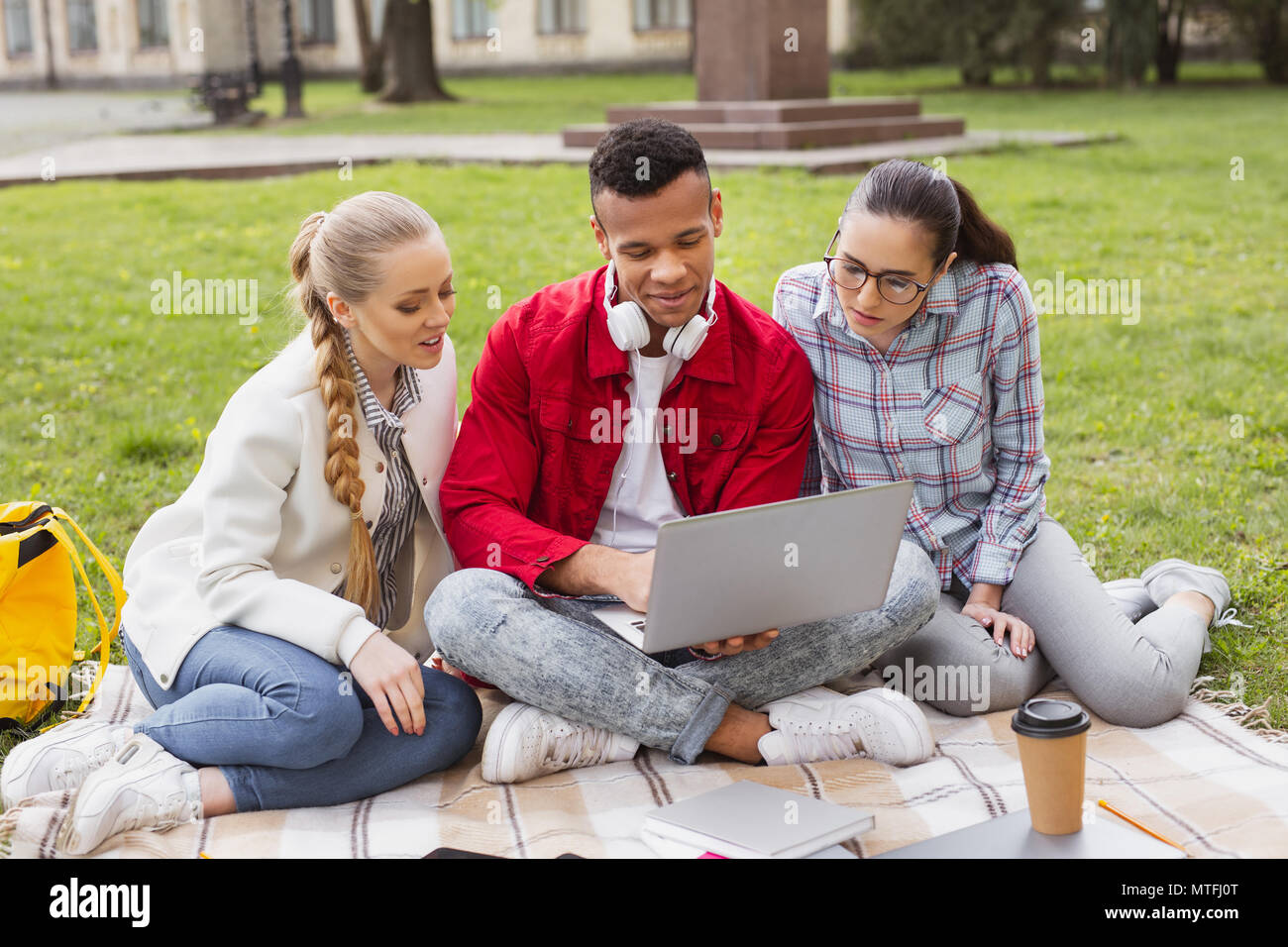 Master degree students watching memorable photos on laptop - Stock Image