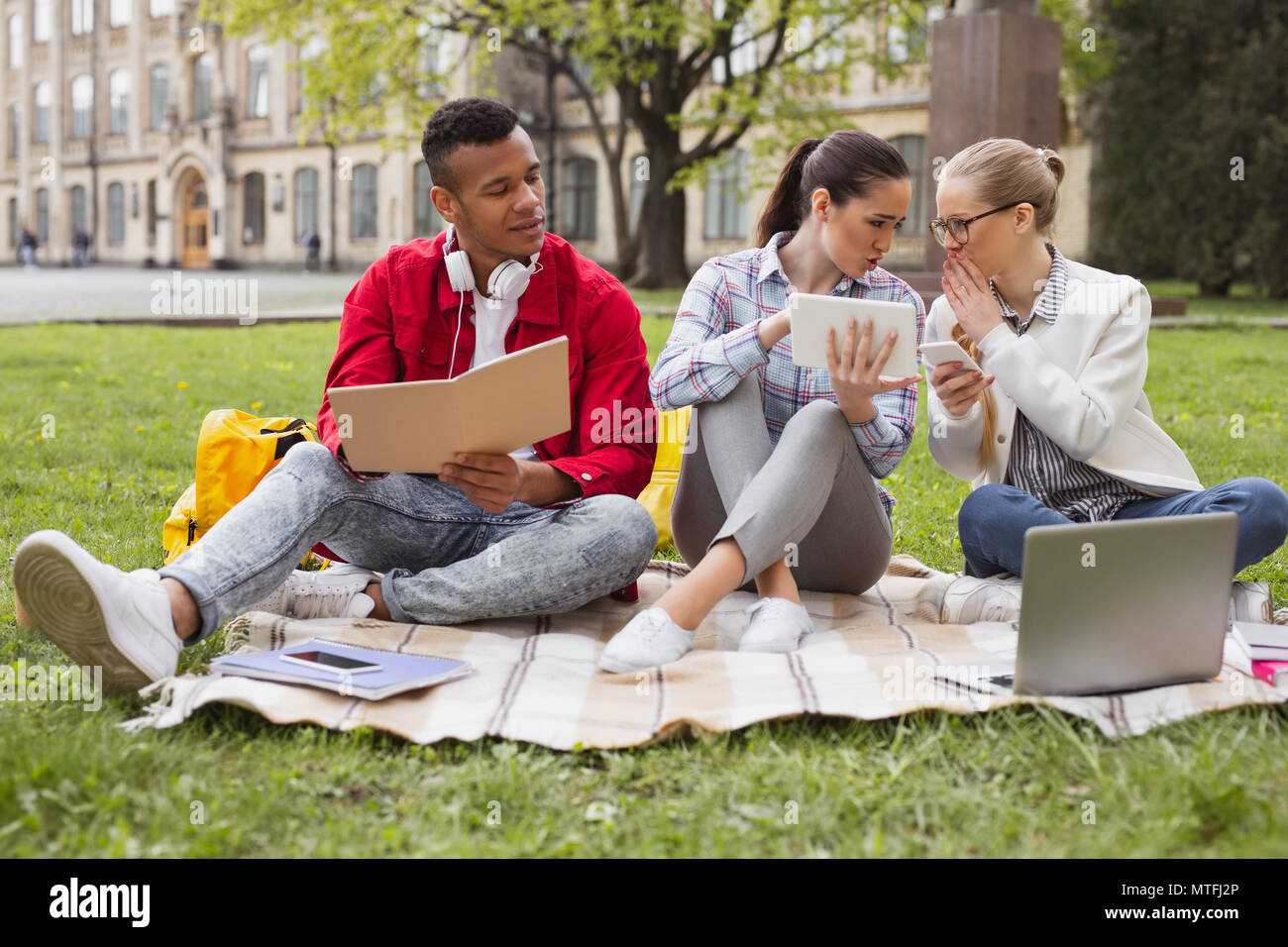 Three students discussing current world events - Stock Image