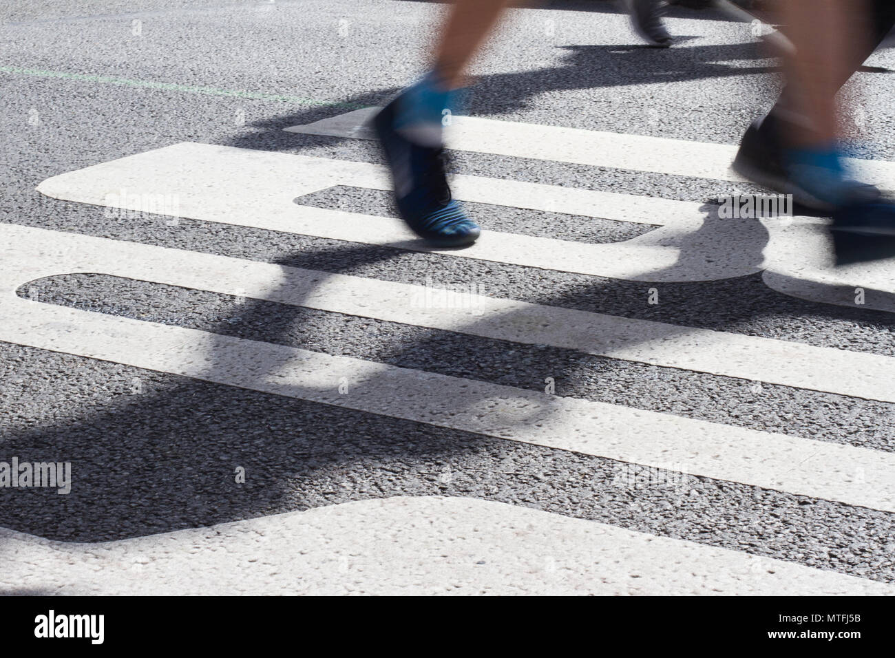 closeup side view of marathon runners feet and legs with motion blur running in the light of the morning on city tarmac road - Stock Image