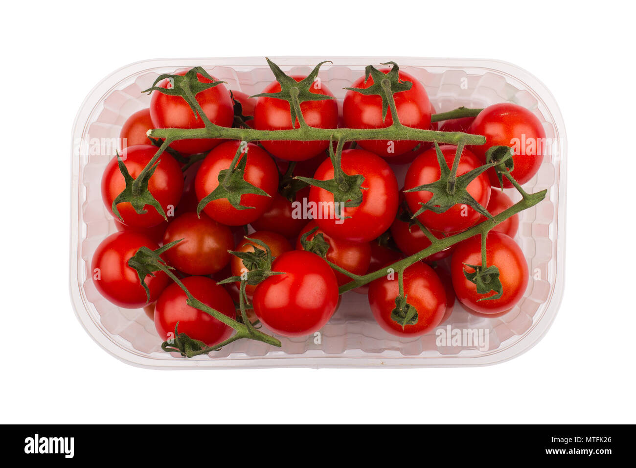 top view closeup detail of fresh red cherry tomatoes with green leaves  in open plastic transparent packaging container isolated on white background - Stock Image