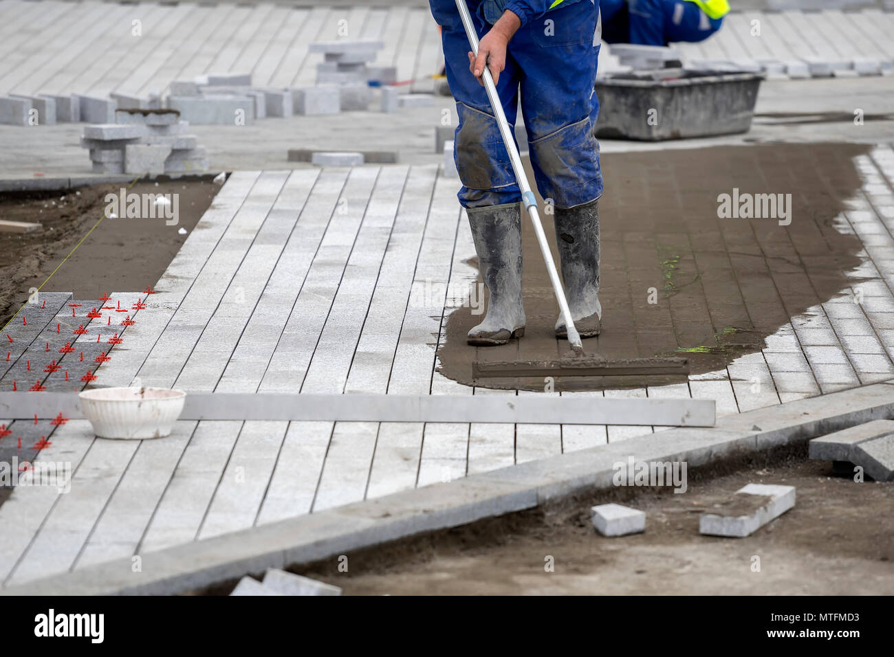Install paver sidewalk with paving stones, using spacers to achieve consistency between tiles and involves working sand down between the paver joints  - Stock Image