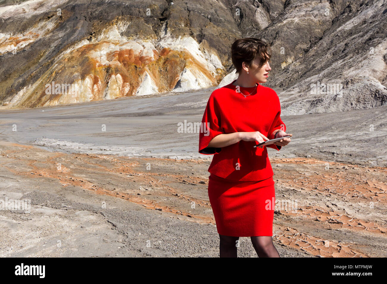 a woman in a business red dress with a tablet in her hands looks around in bewilderment, being in a desert - Stock Image