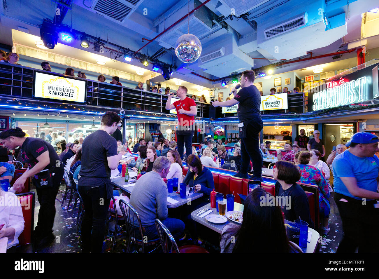 Waiters performing songs from the musicals at Ellens Stardust Diner restaurant, while diners look on, Broadway, New York city USA - Stock Image