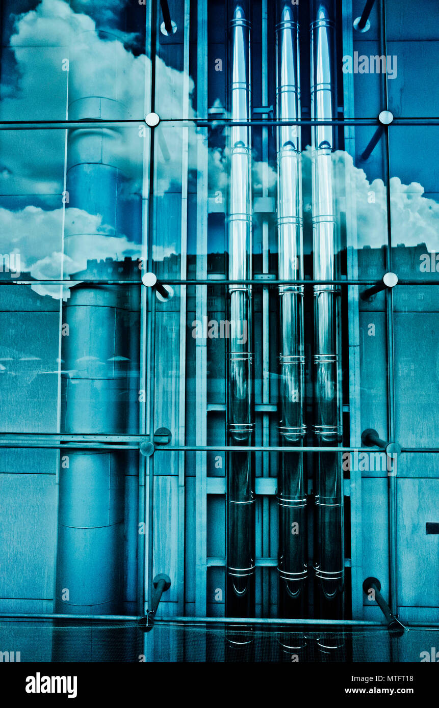 clouds reflected in a glass wall behind which are modern industrial tubes and pipes - Stock Image