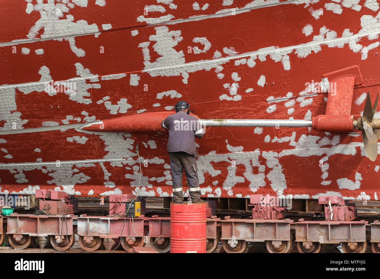 Welder working on a red boat in need to paint, dry dock, market district, cape town, South Africa - Stock Image