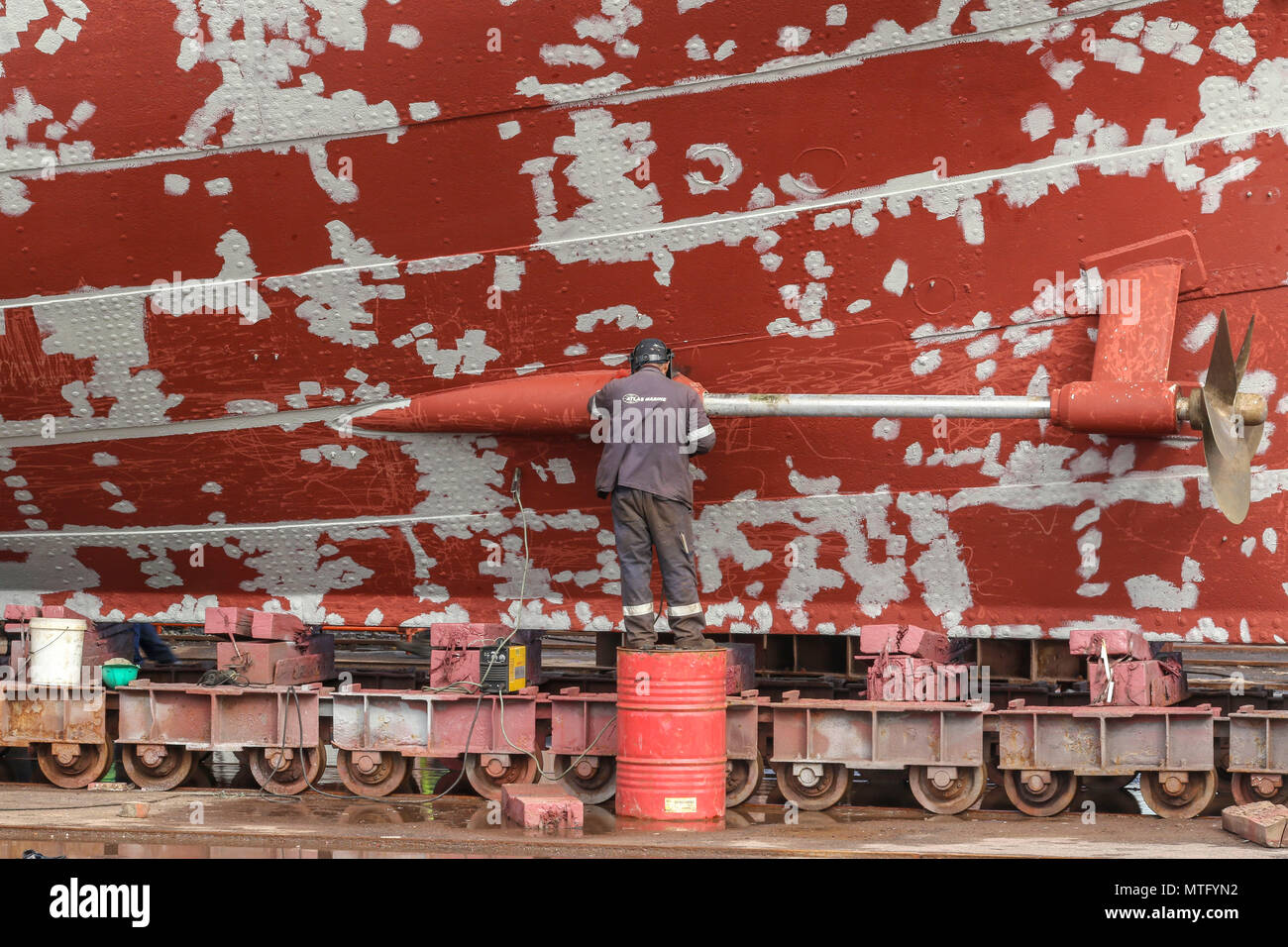 Welder working on a red boat in need to paint, dry dock, Harbour district, cape town, South Africa - Stock Image