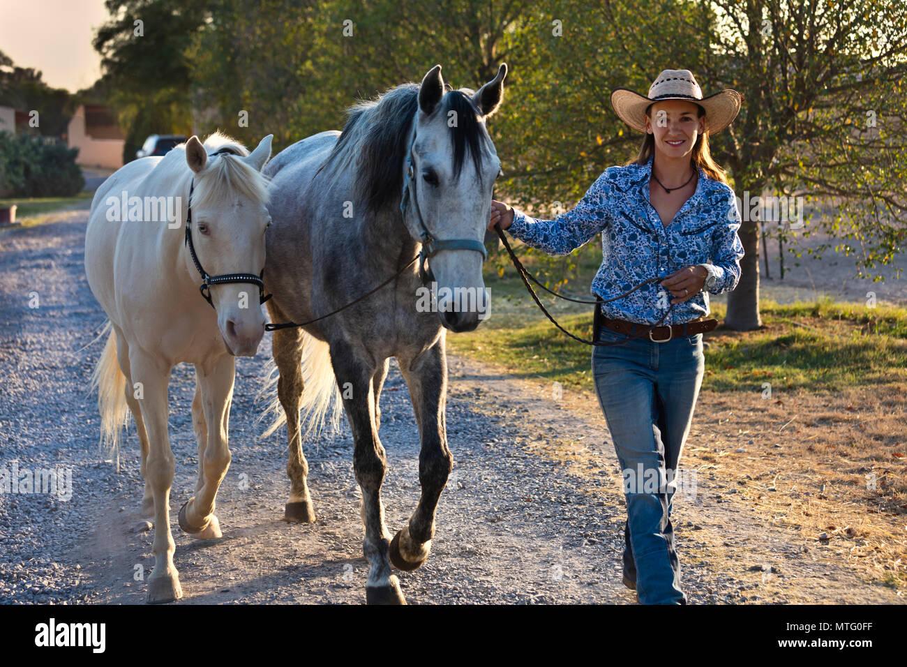 Katja Smith walks a white horse and Lucitano at Granitas de Animas Ranch - SAN MIGUEL DE ALLENDE, MEXICO - Stock Image