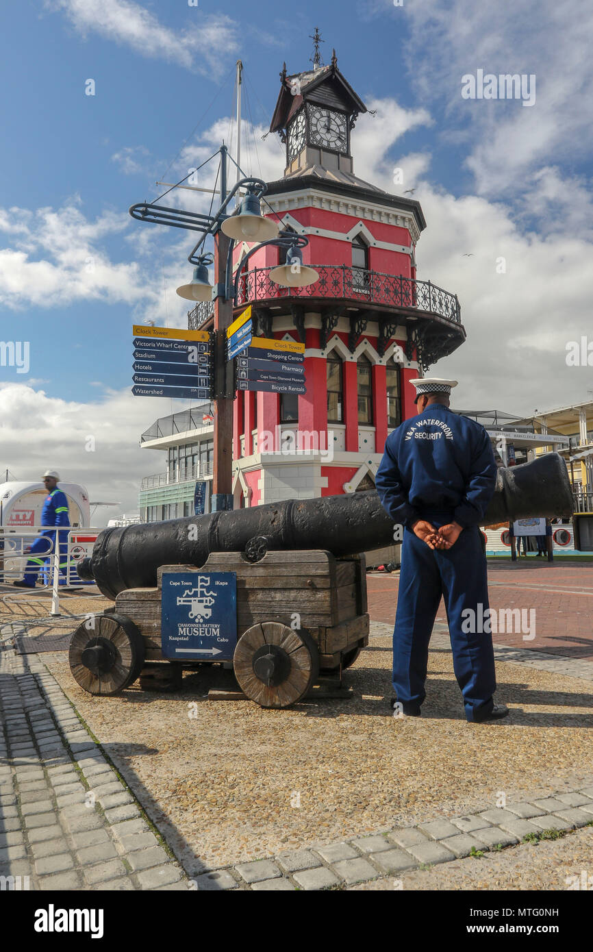 Clock, cannon and security guard on the cape town harbour, cape town, south africa - Stock Image