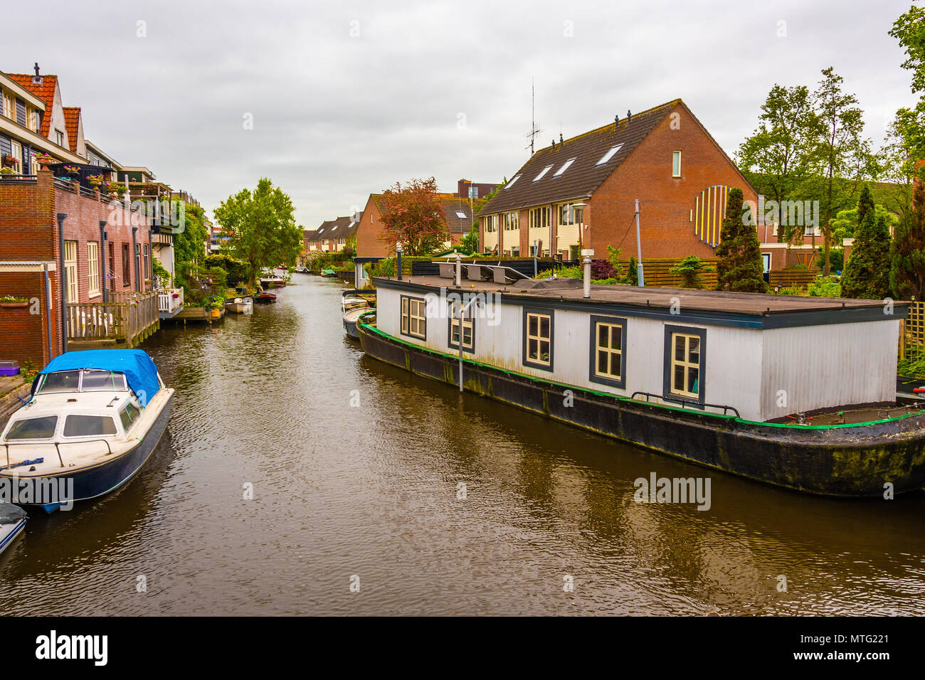 canal and different types of housing surrounding it in a suburb of the city of alkmaar netherlands holland - Stock Image