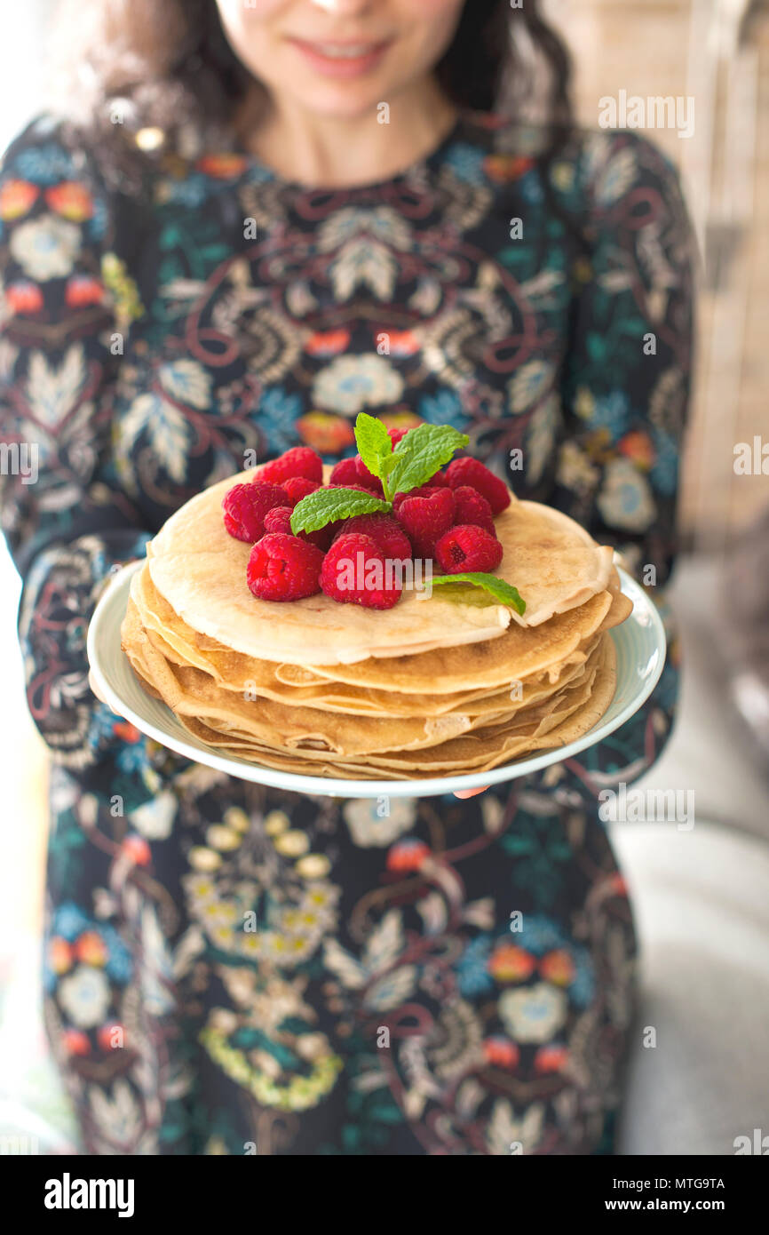 Photo of happy young woman standing at the kitchen in home cooking. Focus on pancakes. - Stock Image