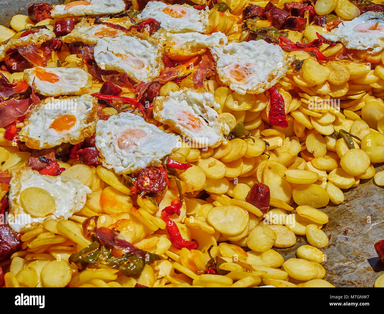 Spanish eggs. Fried eggs with chorizo, potatoes and peppers to the frying pan. Spanish street food. Stock Photo
