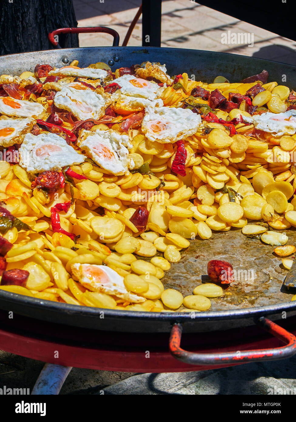 Spanish eggs. Fried eggs with chorizo, potatoes and peppers to the frying pan. Spanish street food. - Stock Image