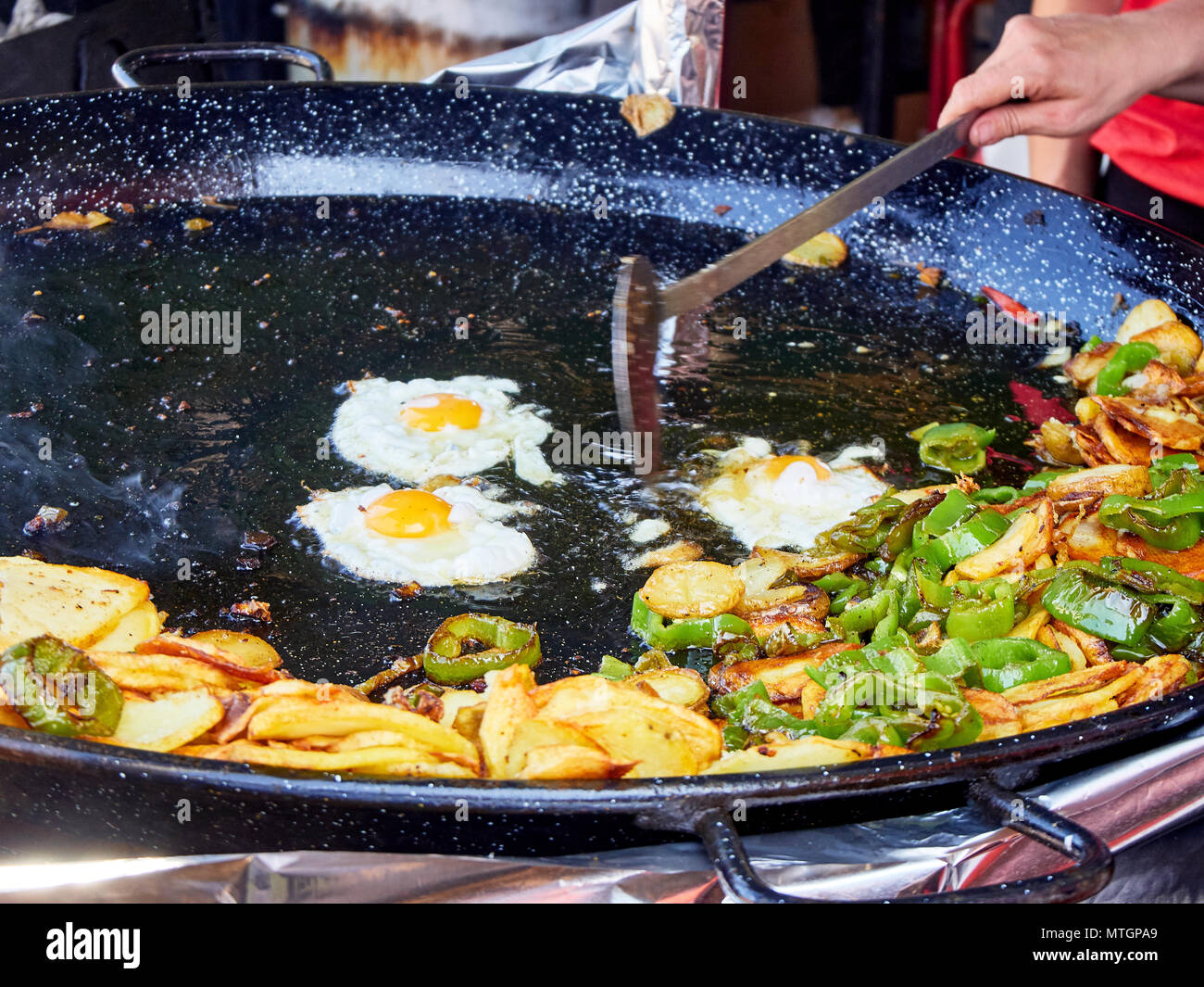 Spanish eggs in progress. Fried eggs with potatoes and peppers to the frying pan. Spanish street food. - Stock Image