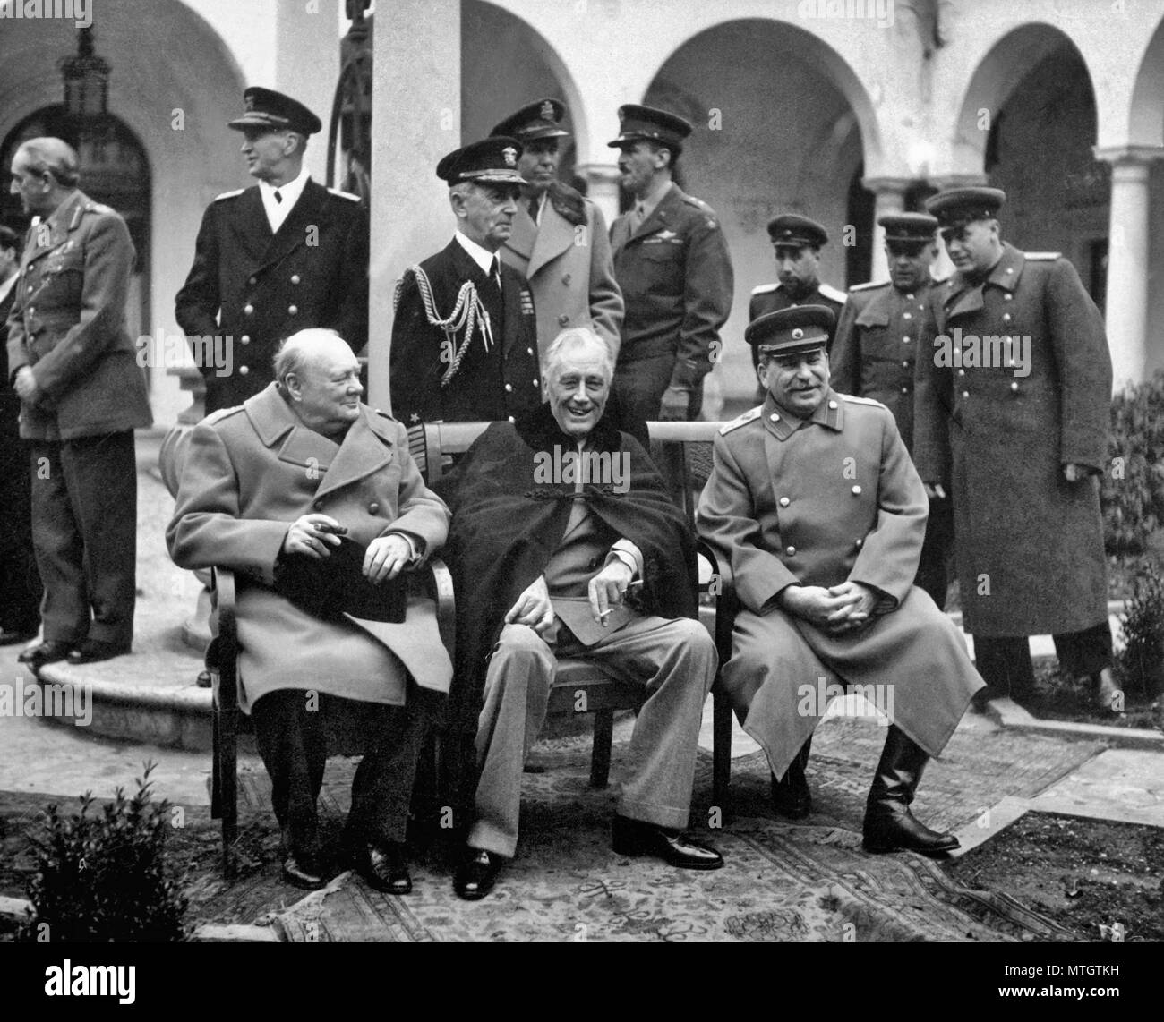 British Prime Minister Winston Churchill, U.S. President Franklin Roosevelt, and Soviet leader Joseph Stalin met at Yalta in February 1945 to discuss their joint occupation of Germany and plans for postwar Europe. Behind them stand, from the left, Field Marshal Sir Alan Brooke, Fleet Admiral Ernest King, Fleet Admiral William D. Leahy, General of the Army George Marshall, Major General Laurence S. Kuter, General Aleksei Antonov, Vice Admiral Stepan Kucherov, and Admiral of the Fleet Nikolay Kuznetsov. February 1945. Stock Photo