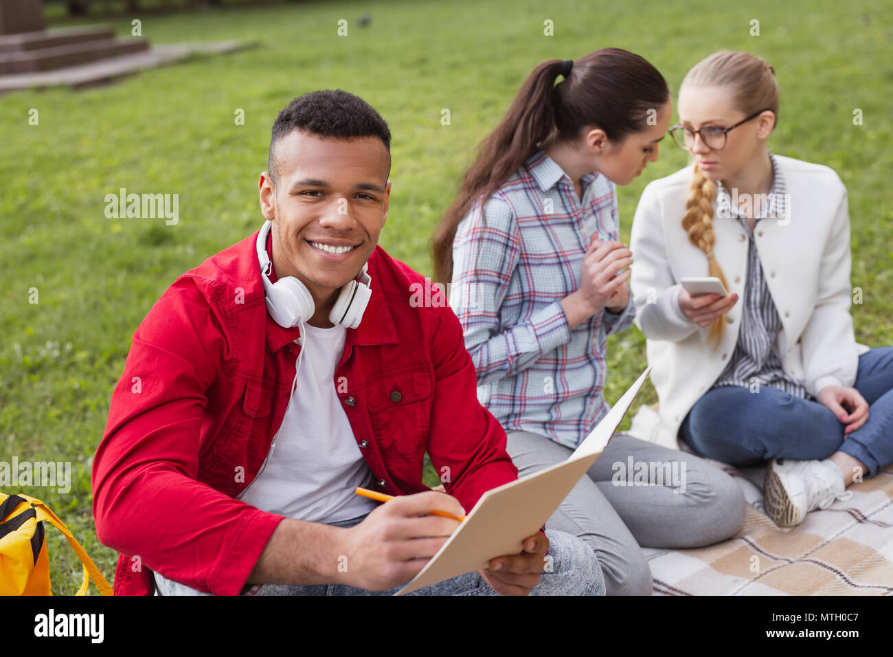 Smiling exchange student writing composition for contest - Stock Image