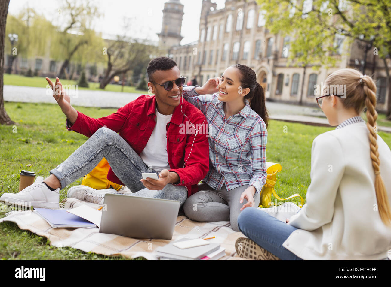 Millennial couple listening to music via earphones - Stock Image