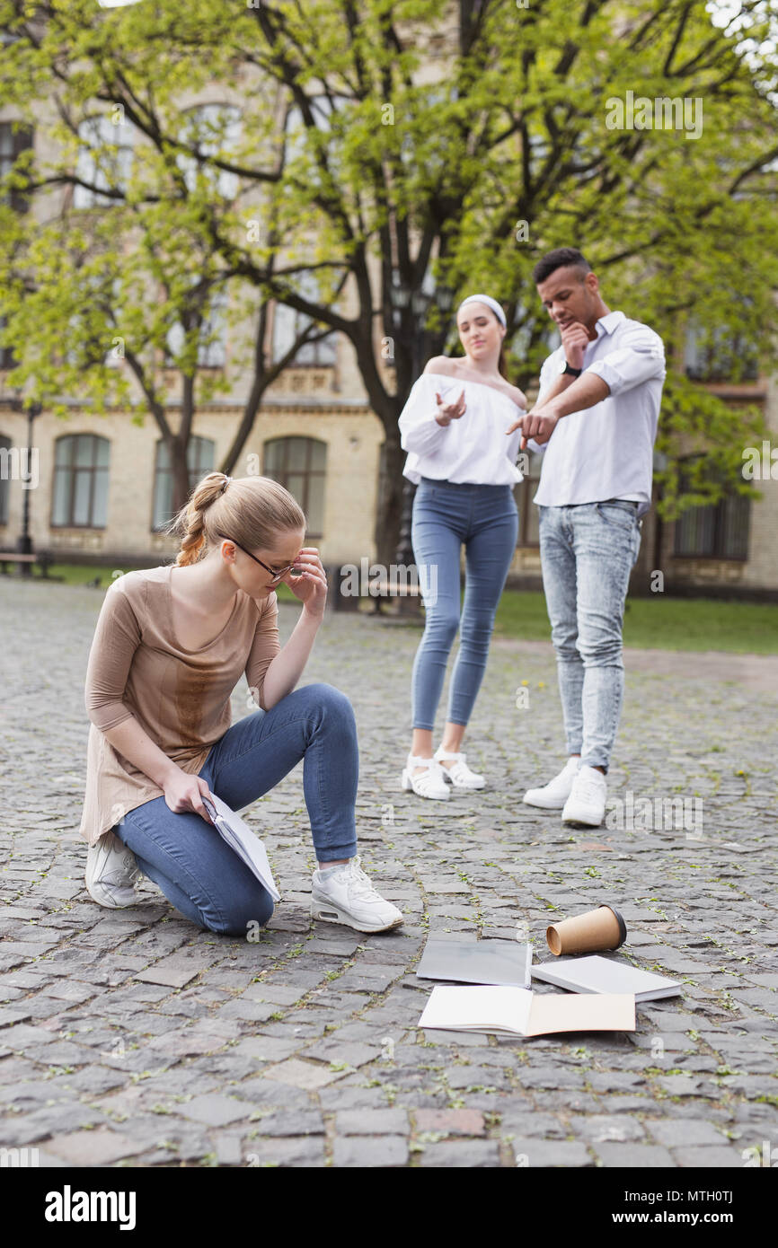 Two insulting students abusing their fellow student - Stock Image
