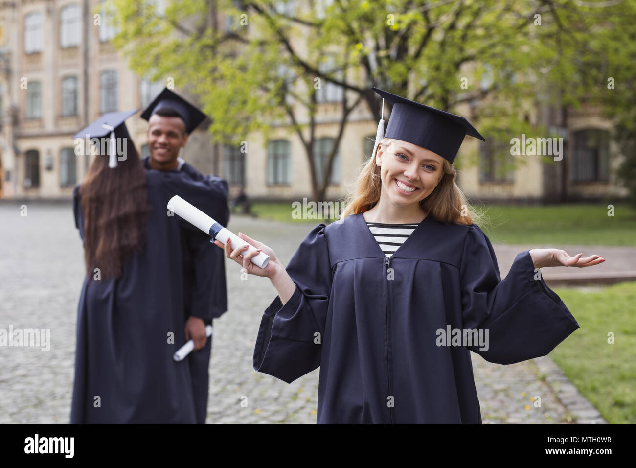 Blonde-haired graduate feeling unbelievable after receiving diploma Stock Photo